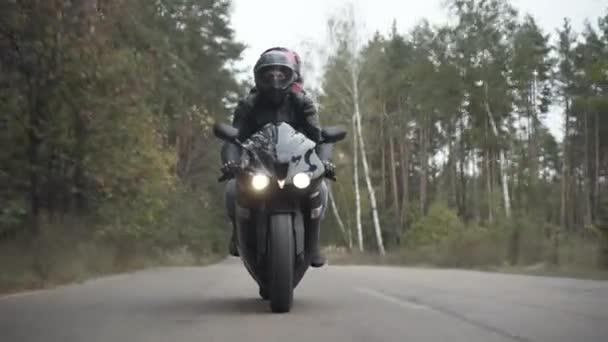 Široký záběr mladého motocyklisty v helmě na koni s přítelkyní na zadním sedadle. Portrét sebevědomého muže jedoucího na motorce po jarní nebo podzimní silnici v zatažený den. Životní styl a příroda.
