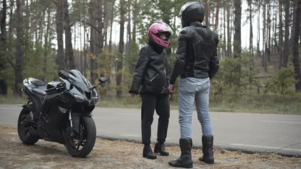 Široký záběr mladých motocyklistů, jak se hádají venku, když je zataženo. Naštvaná nervózní běloška, která dává růžovou helmu muži z Blízkého východu a odchází. Konfliktní koncept.