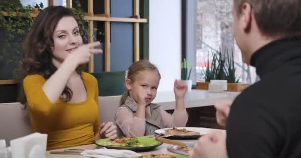 Fröhlicher Vater, Mutter und Tochter tanzen im Pizzeria. Positive kaukasische Familie beim Essen in der Pizzeria drinnen. Lebensfreude und Lifestyle-Konzept. Cinema 4k ProRes Hauptquartier.