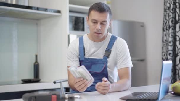 Šťastný mladý brunetka služba muž počítat peníze s úsměvem a dávat dolary do kapsy uniformy. Portrét profesionálního bělošského opraváře s platbou za práci v bytě v interiéru.