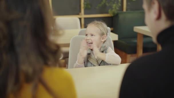 Fröhlich-charmantes kleines Mädchen klatscht als Kellner, der Pizza ins Restaurant bringt. Verschwommene Eltern, die vorne sitzen und ihre Tochter bewundern. Glückliche kaukasische Familie speist in Pizzeria.