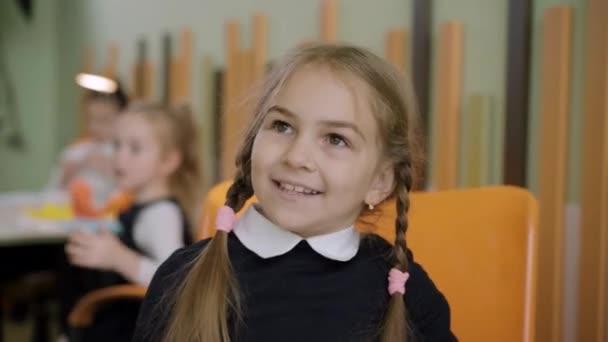 Közelkép egy izgatott kislányról, aki beszél és mosolyog az asztalnál ülő osztályteremben. Pozitív aranyos kaukázusi iskolás lány tanul vagy tanul az állami iskolában. Oktatás és életmód.