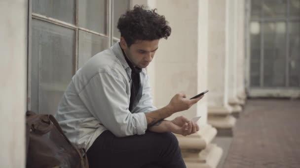 Koncentrált fiatalember nézi a névjegykártyát és a telefonszámot az okostelefonon. Barna hajú fehér fickó portréja, amint hív valakit, aki kint ül a városi utcában..