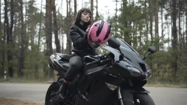 Široký portrét sebevědomé ženy, jak si nasazuje růžovou motocyklovou helmu. Krásná mladá běloška žena biker sedí na černé motorce v kožené bundě. Svoboda a závodní koncept.