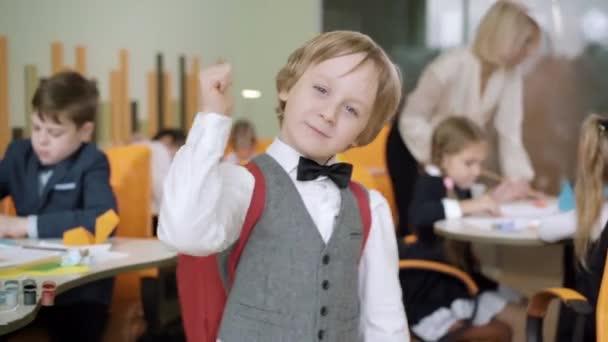 Portrét roztomilého šťastného školáka ukazujícího palec nahoru a usmívajícího se na kameru ve třídě. Šťastný malý kavkazský chlapec pózuje se spolužáky studium a učitel výuky v pozadí.