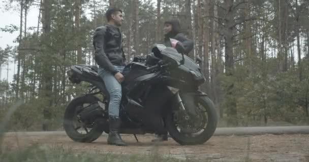 Boční pohled na motocyklisty sedí na černé motorce jako usmívající se žena přichází a mluví. Široký záběr pozitivních mladých mezirasových párů motorkářů venku. Cinema 4k ProRes HQ.