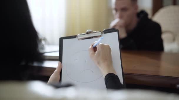 Schießen über die Schulter einer kaukasischen Frau, die ein trauriges Gesicht auf Papier zeichnet, während ein verschwommener Mann im Hintergrund im Büro eines Psychologen sitzt. Unerkannter Berufsarzt unterstützt Patient.