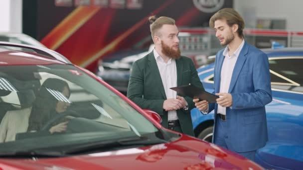 Mladý úspěšný kavkazský podnikatel a sebevědomý prodejce aut mluví v showroomu jako krásná žena sedí na sedadle řidiče ve vozidle. Muž kupující automobil od prodejce v prodejně.