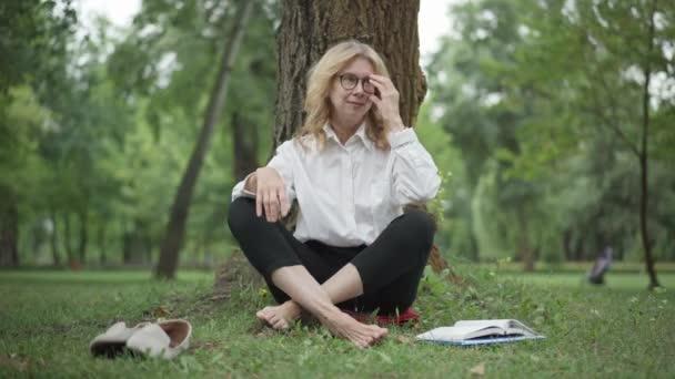 Portrét sebevědomé obchodnice středního věku, která si sundává brýle a sedí v lotosu, pózuje v letním parku. Široký záběr krásné elegantní ženy meditující venku. Životní rovnováha.