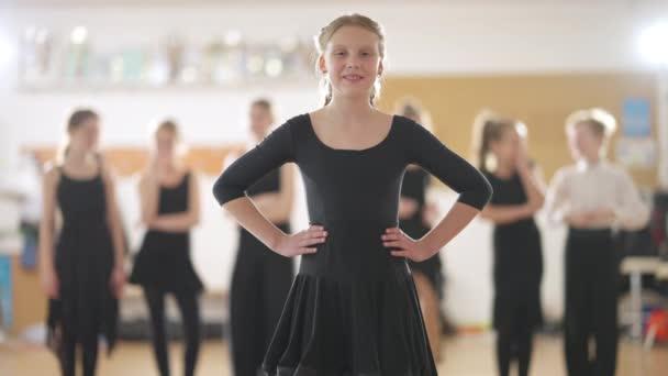 Magabiztos, képzett tinédzser lány áll a táncstúdióban, nézi a kamerát, mosolyog és pukedlizik. Tehetséges kaukázusi tinédzser portréja, aki tánciskolában pózol homályos osztálytársakkal a háttérben.