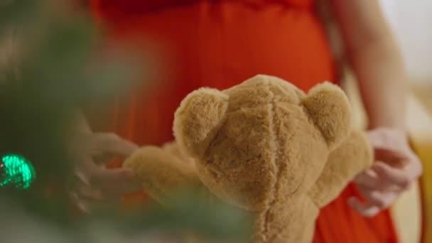 Teddymaci közelről fehér nőstény kezekben, homályos karácsonyfával az elején. Felismerhetetlen terhes nő kezében játék pihen szilveszterkor otthon. Terhesség és öröm.