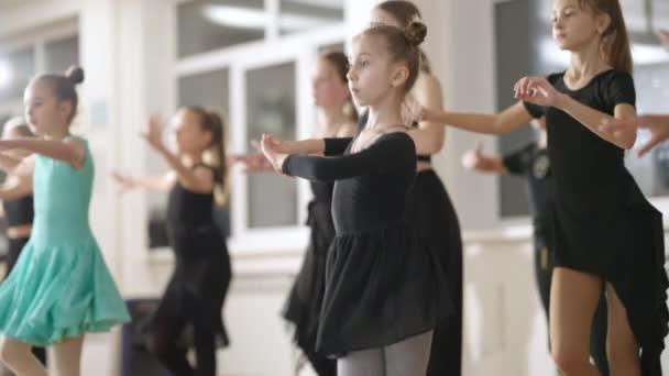Magabiztos gyerekek csoportja, akik latin táncot tanítanak a tánciskolában. Tehetséges kaukázusi lányok és fiúk próbálnak egy lassított felvételű táncstúdióban. Készség- és művészeti koncepció.