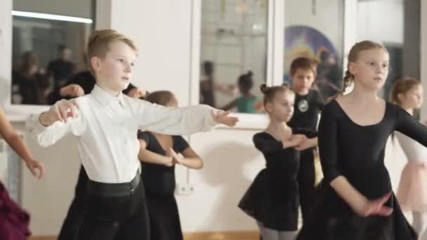 Eine Gruppe kaukasischer Jungen und Mädchen, die in einem Tanzstudio im Spiegel tanzen. Begabte Kinder üben in der Tanzschule lateinamerikanische Standardbewegungen ein. Lebensstil der Kunst.