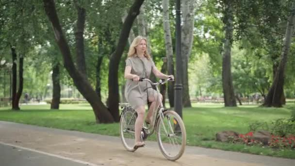 Wide shot of cheerful blond middle aged woman riding bicycle in sunny summer park and stopping. Portrait of excited happy Caucasian lady enjoying bike riding outdoors. Hobby and healthy lifestyle.