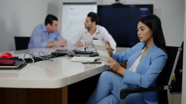 Confident beautiful Asian businesswoman sitting at conference table using tablet with blurred Middle Eastern men talking at background. Portrait of successful young millennial in office indoors.