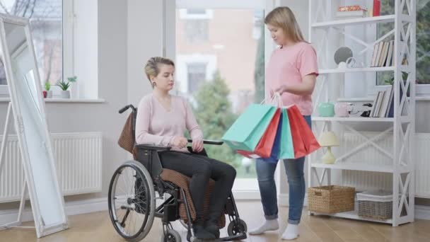 Wide shot portrait of smiling young woman bringing shopping bags for paraplegic friend. Positive Caucasian lady giving gifts to disabled beautiful invalid on wheelchair. Slow motion.