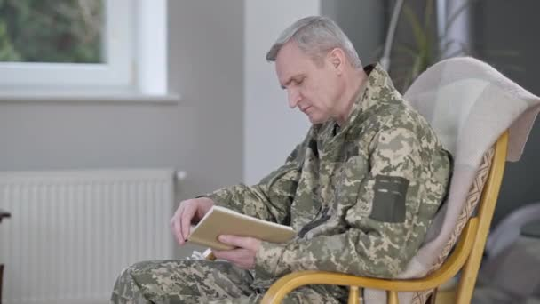 Side view of concentrated absorbed middle aged man in military uniform sitting on rocking chair reading book. Portrait of handsome confident Caucasian soldier or veteran enjoying hobby indoors.