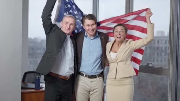 Cheerful American business team posing with national flag in office. Portrait of happy smiling men and woman holding USA national symbol looking at camera rejoicing success. Patriotism and business.