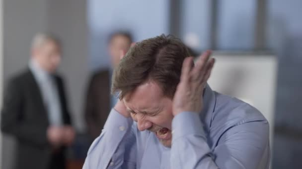 Close-up portrait of angry furious Caucasian man screaming in office indoors. Stressed overwhelmed male employee or manager yelling and holding head in hands with blurred colleagues at background.