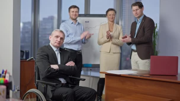 Portrait of confident senior paraplegic man in wheelchair looking at camera with crossed hands as blurred young colleagues clapping at background. Successful disabled Caucasian CEO in office.