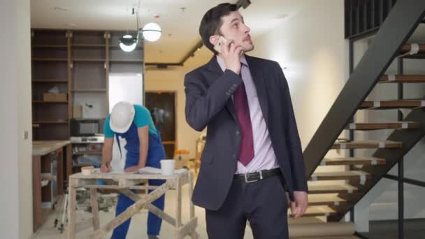 Portrait of real estate agent talking on the phone in new apartment as service man drawing plan at background. Confident handsome young Caucasian man controls condo building indoors.