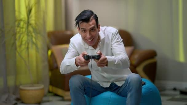 Heiter gutaussehender Mann aus dem Nahen Osten, der zu Hause auf einem Stuhl sitzt und in die Kamera schaut. Porträt eines fröhlich entspannten, unbeschwerten Spielers, der sich im Wohnzimmer ausruht.