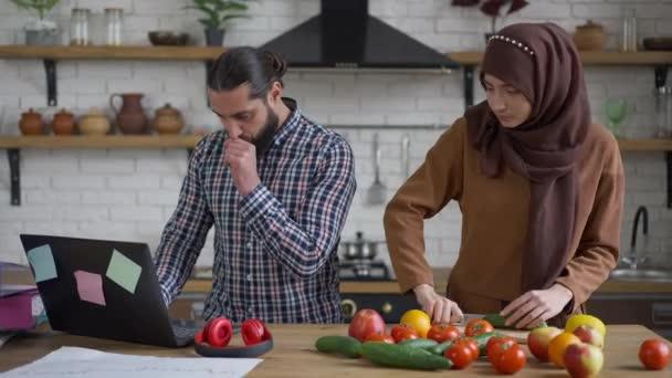 Mladá krásná žena v hidžábu krájení okurky v kuchyni jako zaneprázdněný manžel surfování na internetu na notebooku. Portrét muže ze Středního východu pracující online jako žena vařící zdravý salát. Nový normální.