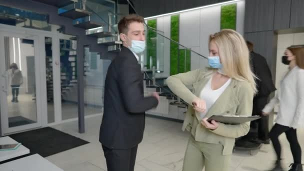 Young confident man and woman in coronavirus face masks touching elbows greeting in office entrance hall talking. Successful elegant male and female business partners meeting indoors discussing