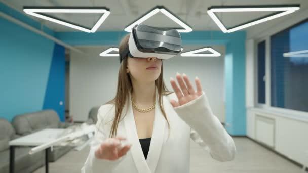 Közepes felvételű portré komoly felszívódott fiatal kaukázusi nőről VR headset-ben, irodai helyiségekben állva, építészeti projektet tervezve. Tehetséges építész a megnövelt belső valóságban.