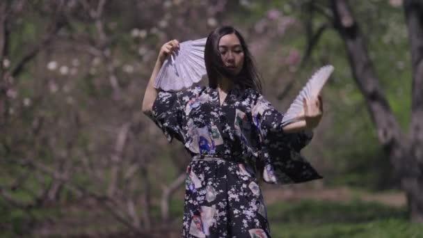 Sebevědomá Asiatka v kimonu tančí s fanoušky v sakura zahradě. Tanec půvabné štíhlé krásné dámy ve slunném letním jarním parku venku. Koncept přírody a ženskosti.
