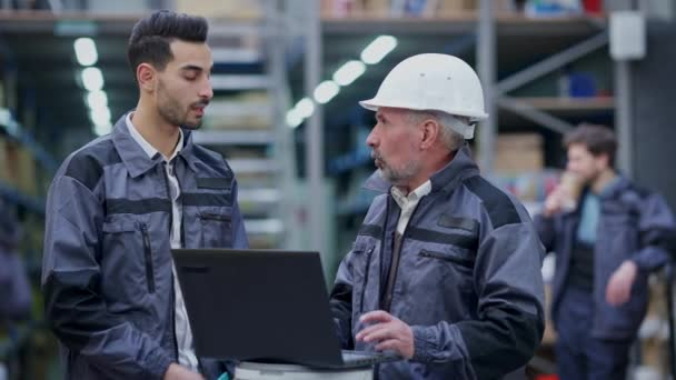 Serious dissatisfied Caucasian manager in hard hat scolding incompetent Middle Eastern young employee in warehouse. Handsome man sighing as boss talking showing laptop. Failure and conflict.