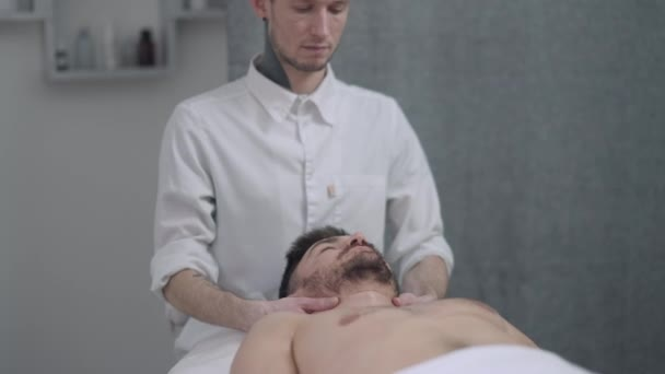 Handsome Caucasian man lying on massage bed as concentrated male masseur massaging neck muscles in slow motion. Relaxed client with closed eyes enjoying therapeutic massage in spa indoors.