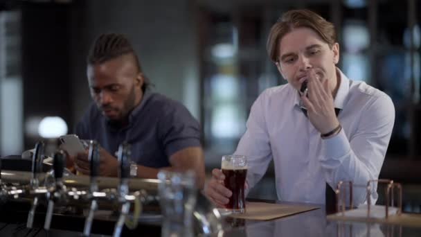 Portrait of drunken Caucasian man sitting in bar with dark lager beer and car keys as blurred African American friend ordering taxi online in smartphone app. Responsible driving and booze.