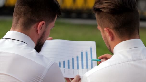 Two partners analyzing bar chart