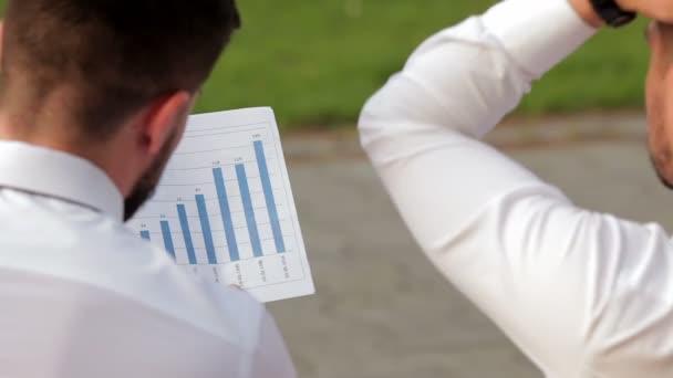 Two partners analyzing bar chart