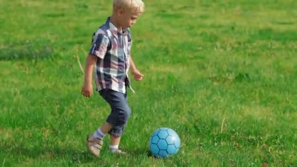Elementary aged boy kicking ball in the field