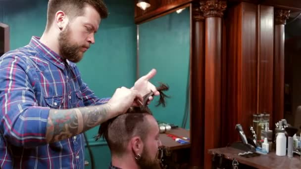 Beard Barber Making Haircut To Hipster Client Stock Video