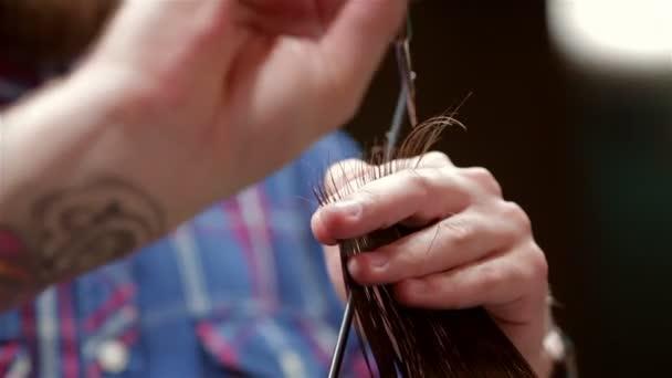 Barbiere di barba che rende il taglio di capelli al client hipster