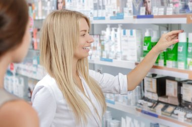 Beautiful girl pharmacist helping a customer