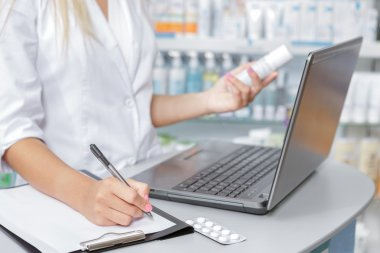 Close up of a druggist making notes from the laptop