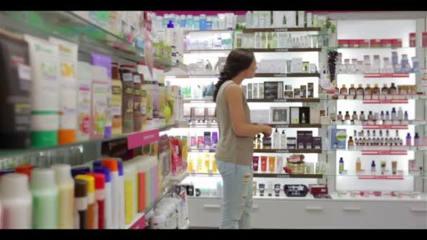 schöne junge Frau auf der Suche nach dem richtigen Shampoo