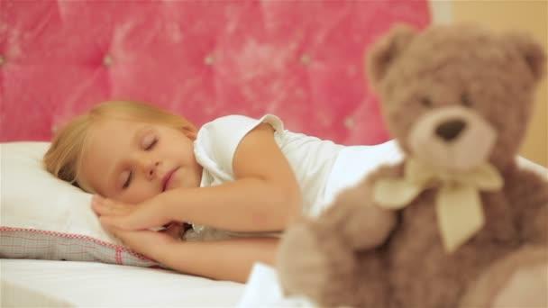 Aranyos kislány alvó mellett ő medve plüss
