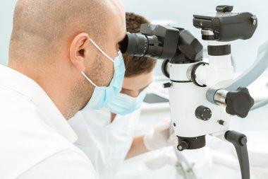 Dentist using dental microscope during inspection