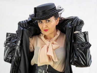 Woman in black PVC mac wearing a hat