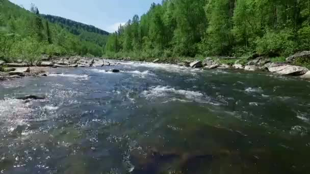 flying camera over the mountain river is very low over the water (quadrocopter)