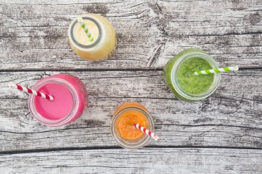 Various colorful fruit smoothies in glass bottles