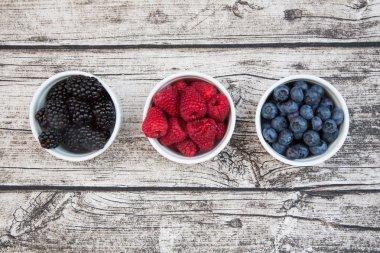 Wild berries, Raspberries, blueberries and blackberries in bowls