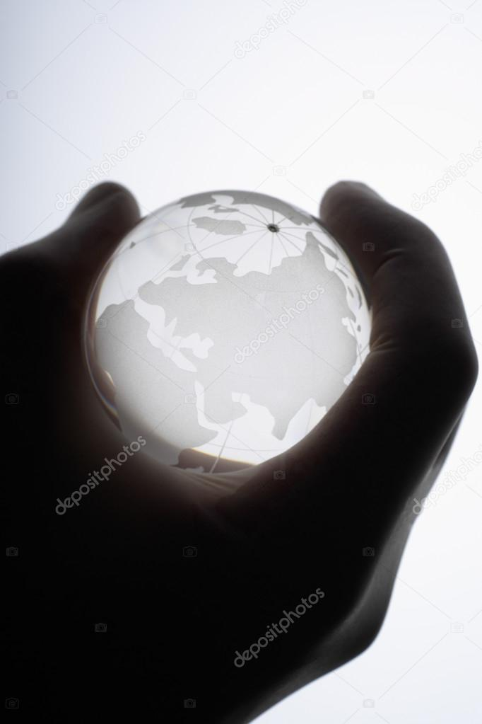 Human hand with medical gloves gripping glass globe against whit