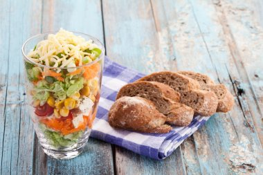 Close up of vegetable and cheese layered salad in glass with bre