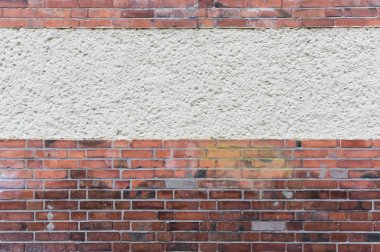 Outside wall with plastered area between red clinker brick, text